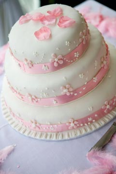 three tier small simple wedding cake with pink ribbon