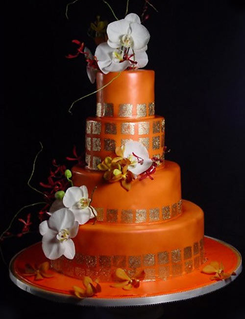 Gorgeous orange retro four tier wedding decorated with square gold leaf patterns and white ochids and orange flowers