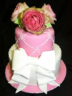 two tier white and pink vintage style, shabby chic fondant wedding cake decorated with a large white fondant bow