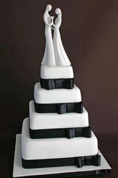 Four tier black and white wedding cake decorated with black satin ribbon and bows around each tire