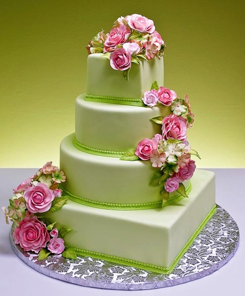 Four tier, vibrant green wedding cake decorated with pretty pink cascading flowers