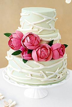 Creative three tier wedding cake decorated with white branch like fondant designs and large stunning pink hand made flowers