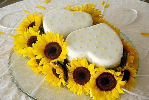 Sunflower heart shaped wedding cakes decorated with yellow sunflowers