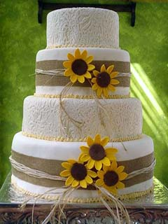 Four tier round white and straw wedding cake decorated with handcrafted yellow sunflowers