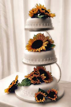 Three white satellite wedding cakes decorated with yellow sunflowers