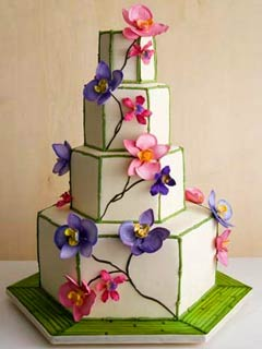 Interesting four tier hexagon wedding cake, decorated with green bamboo trimming in all the corners and pink and purple orchid flowers