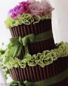 Unique, two tier brown, green and pink wedding cake wrapped with olive green satin ribbon