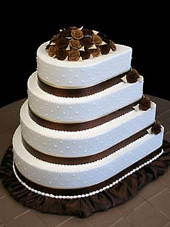 Unusually shaped white and brown wedding cake in a teardrop shape. Decorated with brown satin ribbon, brown skerting around the bottom tier
