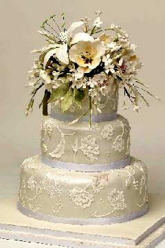 Small, round, classically designed three tier white Victorian lace wedding cake