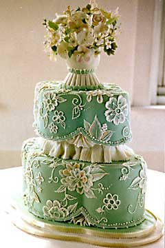 Small, two tier, green Victorian style wedding cake decorated with white floral lace and lacy scrolls